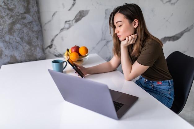 Glimlachende jonge aziatische vrouw die mobiele telefoon gebruikt terwijl ze op een keuken zit met een laptop