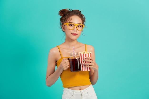 Glimlachende jonge aziatische vrouw die popcorn eet en soda drinkt die over blauw wordt geïsoleerd.