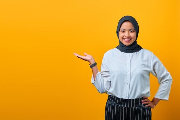 Glimlachende jonge aziatische vrouw die product voorstelt en camera op gele achtergrond kijkt