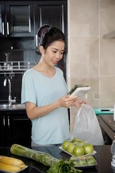 Glimlachende jonge aziatische vrouw in t-shirt die in de keuken staat en naar een komkommercontainer kijkt terwijl ze producten uit een papieren zak uitpakt