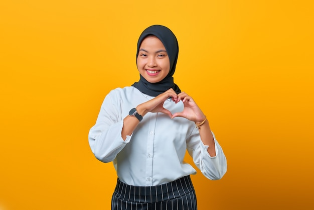 Glimlachende jonge aziatische vrouw maakt hartteken op gele achtergrond