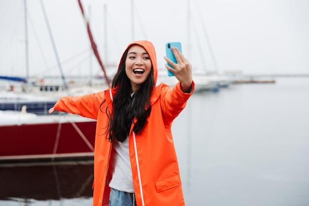 Glimlachende jonge aziatische vrouw met een regenjas die tijd doorbrengt in de buitenlucht aan het kustland en een selfie maakt