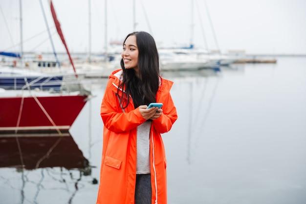 Glimlachende jonge aziatische vrouw met een regenjas die tijd doorbrengt in de buitenlucht aan het kustland, met behulp van mobiele telefoon