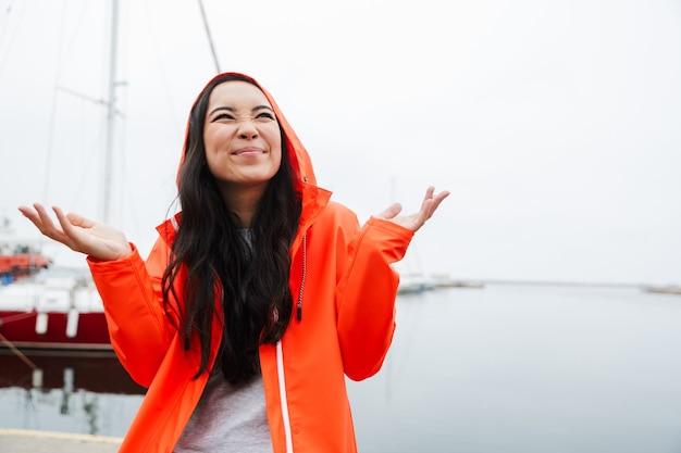 Glimlachende jonge aziatische vrouw met een regenjas die tijd doorbrengt in de buitenlucht aan het kustland, omhoog kijkend