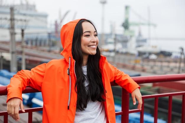 Glimlachende jonge aziatische vrouw met een regenjas die tijd doorbrengt in de buitenlucht aan het kustland, poserend in een capuchon