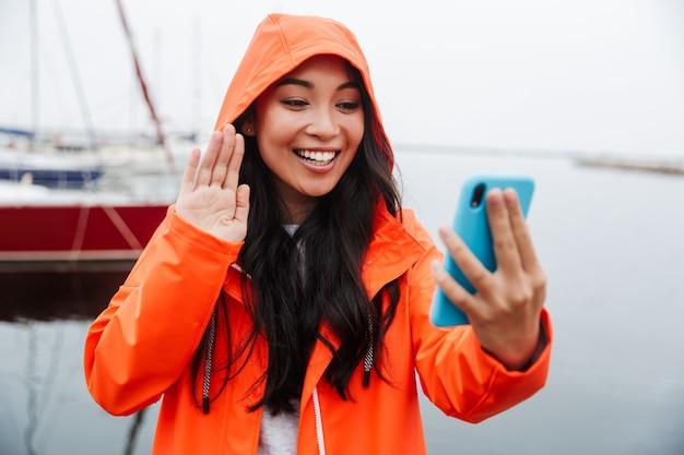 Glimlachende jonge aziatische vrouw met een regenjas die tijd doorbrengt met wandelen in het kustland, een selfie maken, zwaaien