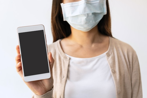 Glimlachende jonge aziatische vrouw met medisch gezichtsmasker met leeg scherm van mobiele telefoon voor vrije ruimte op witte achtergrond. nieuw normaal, voorkom vervuiling en ziekteconcept. ruimte kopiëren