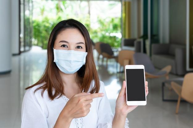 Glimlachende jonge aziatische vrouw met smartphone van de ptotective gezichtsmaskerholding voor exemplaarruimte.