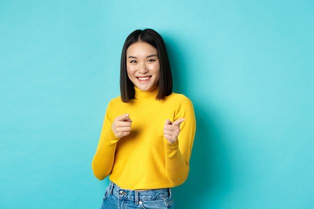 Glimlachende jonge aziatische vrouw wijzende vingers op camera, u kiezen, uitnodigend voor evenement, permanent gelukkig tegen blauwe achtergrond.