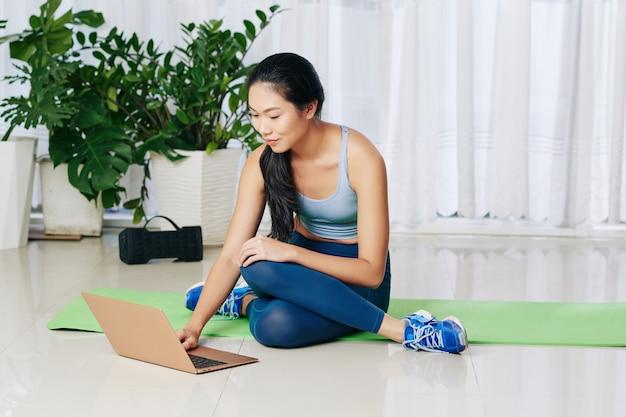 Glimlachende jonge aziatische vrouw zittend op de vloer en online op laptop zoeken naar oefeningsvideo
