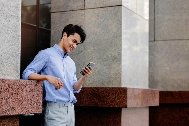 Glimlachende jonge aziatische zakenman die mobiele telefoon in de stad gebruikt