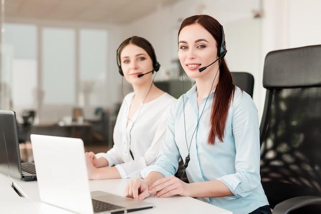 Glimlachende jonge beambte met een hoofdtelefoon die in een call centre, vrouw beantwoordt die met cliënten spreekt