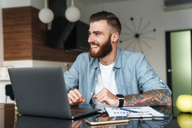 Glimlachende jonge bebaarde man aan het werk op laptopcomputer zittend aan de keukentafel