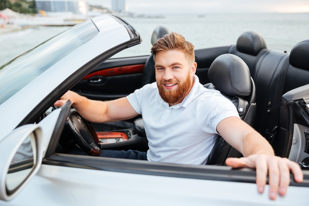 Glimlachende jonge, bebaarde man die uit zijn auto komt