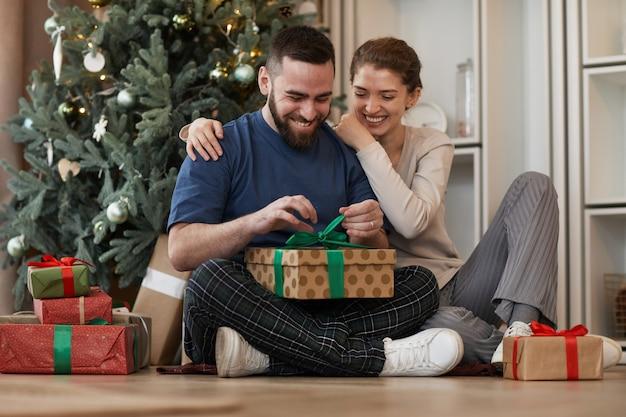 Glimlachende jonge bebaarde man omarmd door vriendin zittend met gekruiste benen tegen kerstboom en...