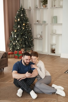 Glimlachende jonge bebaarde man zittend op de vloer in de woonkamer met kerstboom en video tonen op p...