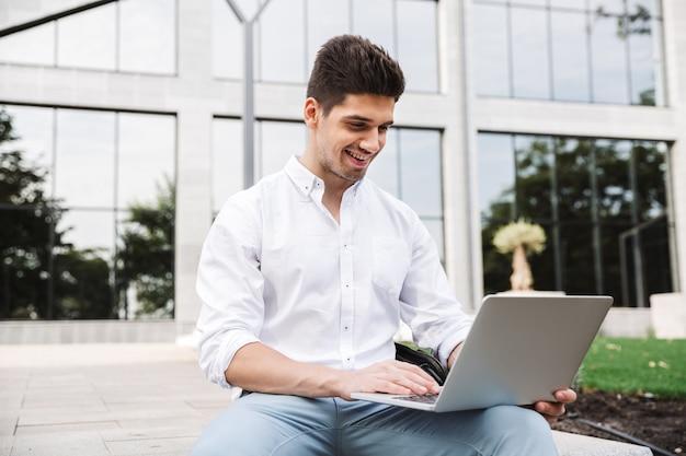 Glimlachende jonge bedrijfsmens die aan laptop computer werkt
