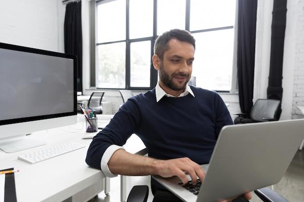 Glimlachende jonge bedrijfsmens die laptop met behulp van