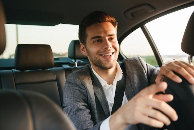 Glimlachende jonge bedrijfsmensenpassagier die taxichauffeur toont