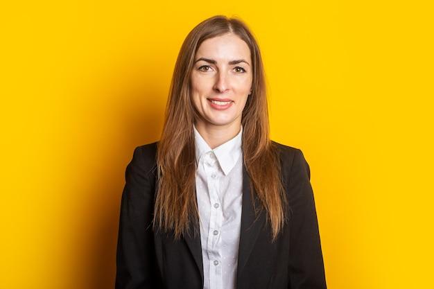 Glimlachende jonge bedrijfsvrouw in een jasje op geel.