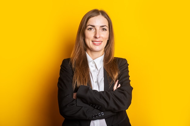 Glimlachende jonge bedrijfsvrouw in een zwart jasje op geel.