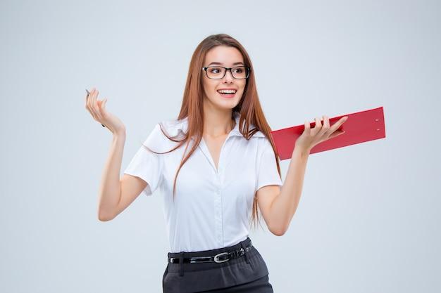 Glimlachende jonge bedrijfsvrouw in glazen met pen en tablet voor notities over een grijze achtergrond