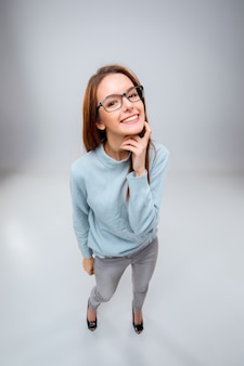 Glimlachende jonge bedrijfsvrouw in glazen op een grijze achtergrond. bovenaanzicht
