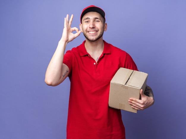 Glimlachende jonge bezorger die een uniform draagt met een doos met een dop die een goed gebaar toont