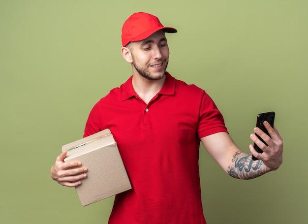 Glimlachende jonge bezorger die een uniform draagt met een dop die een doos vasthoudt en naar de telefoon in zijn hand kijkt