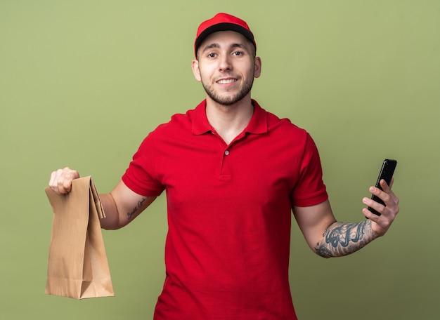 Glimlachende jonge bezorger die een uniform draagt met een pet die een papieren voedselzak met telefoon vasthoudt