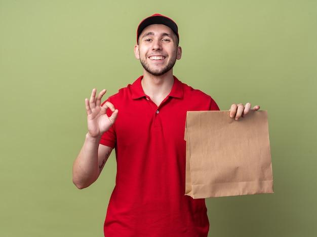Glimlachende jonge bezorger die een uniform draagt met een pet die een papieren voedselzak vasthoudt en een goed gebaar toont