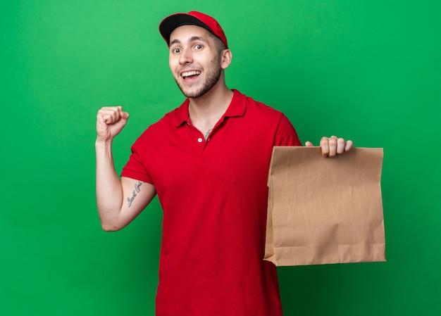 Glimlachende jonge bezorger die een uniform draagt met een pet die een papieren voedselzak vasthoudt en een ja-gebaar toont