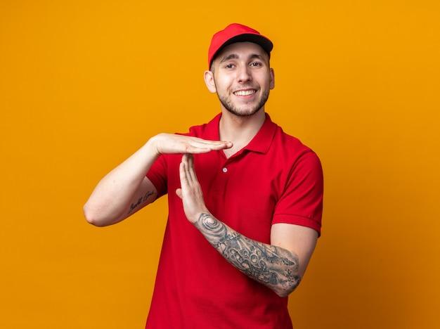 Glimlachende jonge bezorger die een uniform draagt met een pet die een time-outgebaar toont