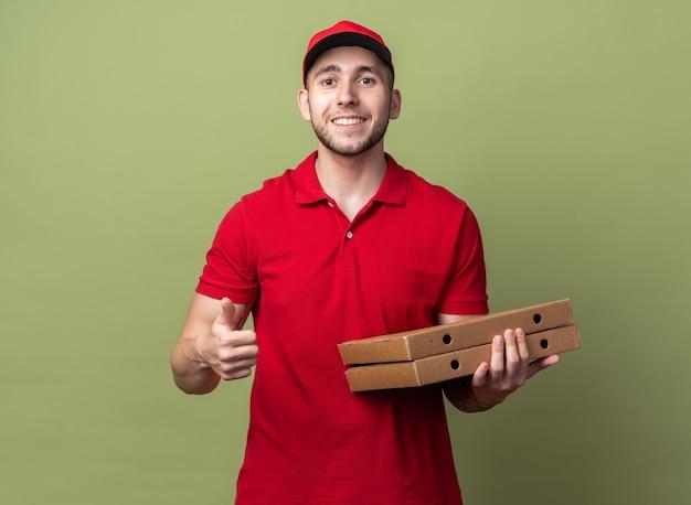 Glimlachende jonge bezorger die een uniform draagt met een pet die pizza vasthoudt en dozen met duim omhoog laat zien