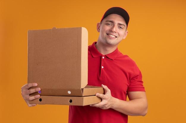 Glimlachende jonge bezorger die eenvormig met glb draagt die pizzadoos opent die op oranje muur wordt geïsoleerd