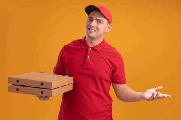 Glimlachende jonge bezorger die eenvormig met glb draagt die pizzadozen houdt die hand spreidt die op oranje muur wordt geïsoleerd