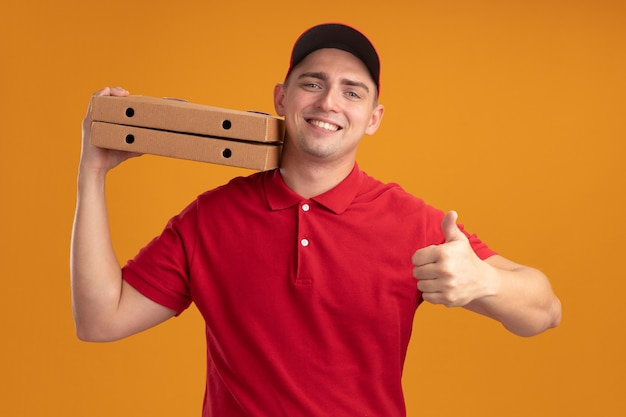 Glimlachende jonge bezorger die eenvormig met glb draagt die pizzadozen op schouder houdt die duim tonen die omhoog op oranje muur wordt geïsoleerd