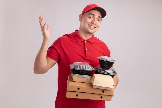 Glimlachende jonge bezorger die eenvormig met glb draagt die voedselcontainers op pizzadozen houdt die hand verspreiden die op witte muur wordt geïsoleerd