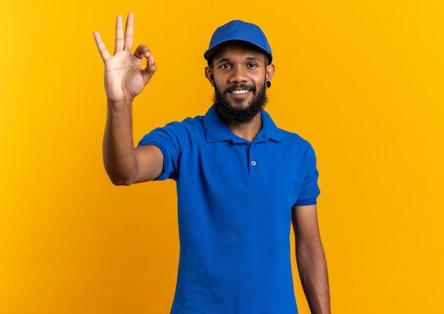 Glimlachende jonge bezorger die ok teken gebaren geïsoleerd op een oranje muur met kopie ruimte