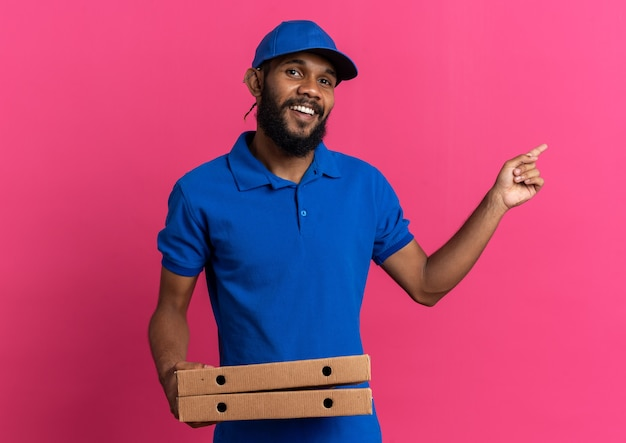 Glimlachende jonge bezorger die pizzadozen vasthoudt en naar de zijkant wijst geïsoleerd op een roze muur met kopieerruimte