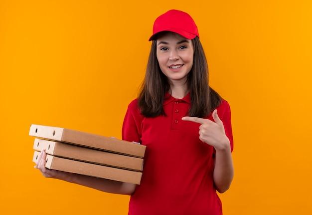 Glimlachende jonge bezorger die rode t-shirt in rode pet draagt die een pizzadoos houdt en met een vinger op geïsoleerde oranje muur wijst