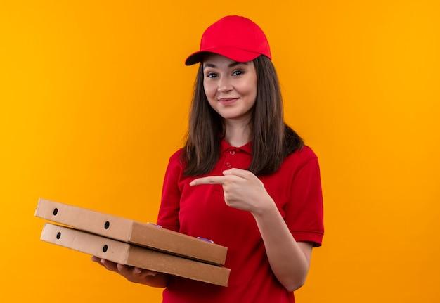 Glimlachende jonge bezorger die rode t-shirt in rode pet draagt die een pizzadoos houdt en vingers op geïsoleerde gele muur wijst