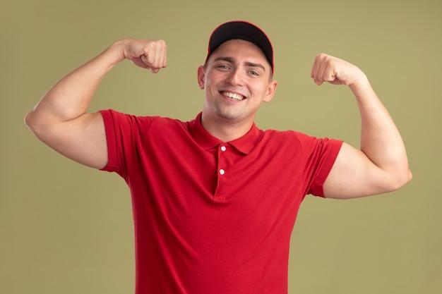 Glimlachende jonge bezorger die uniform en pet draagt die sterk gebaar tonen dat op olijfgroene muur wordt geïsoleerd