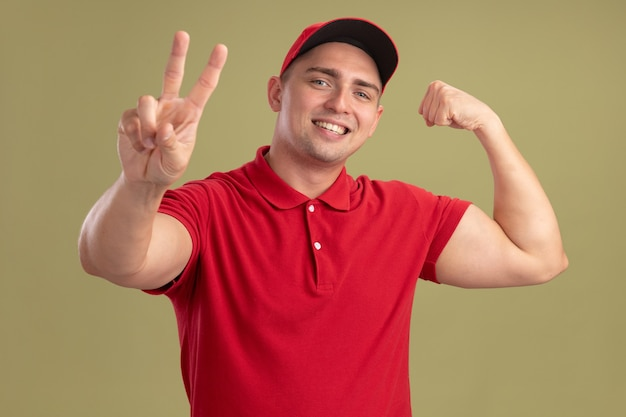 Glimlachende jonge bezorger die uniform en pet draagt die vredesgebaar met sterk gebaar toont dat op olijfgroene muur wordt geïsoleerd