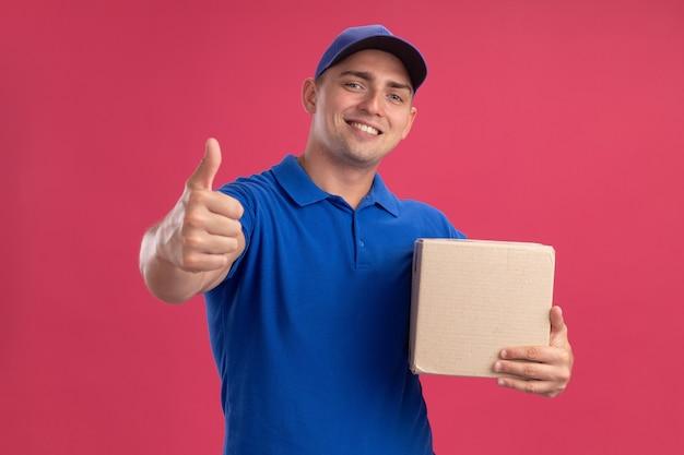 Glimlachende jonge bezorger die uniform met de doos van de glbholding draagt die duim toont die omhoog op roze muur wordt geïsoleerd