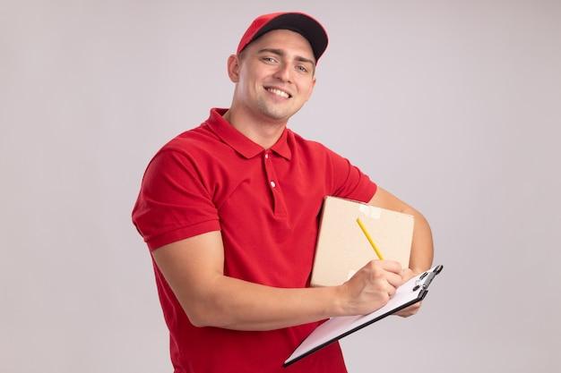 Glimlachende jonge bezorger die uniform met de doos van de glbholding draagt en iets op klembord schrijft dat op witte muur wordt geïsoleerd