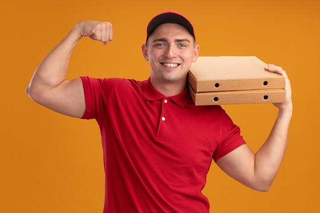 Glimlachende jonge bezorger die uniform met pet draagt die pizzadozen op schouder houdt en sterk gebaar toont dat op oranje muur wordt geïsoleerd