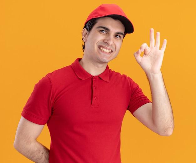 Glimlachende jonge bezorger in blauw uniform en pet die naar de voorkant kijkt en de hand achter de rug houdt met een ok teken geïsoleerd op een oranje muur