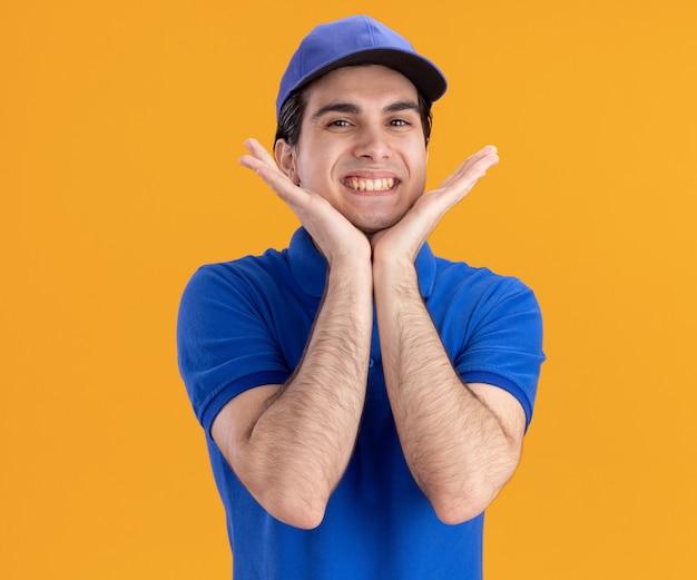 Glimlachende jonge bezorger in blauw uniform en pet die naar de voorkant kijkt en de handen onder de kin houdt, geïsoleerd op een oranje muur