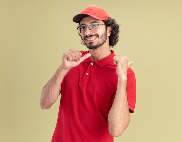 Glimlachende jonge bezorger in rood uniform en pet met bril kijkend naar de voorkant wijzend naar de zijkant geïsoleerd op olijfgroene muur met kopieerruimte